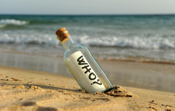 """Flaschenpost am Strand mit dem Wort """"WHO?"""" auf der Schriftrolle."""