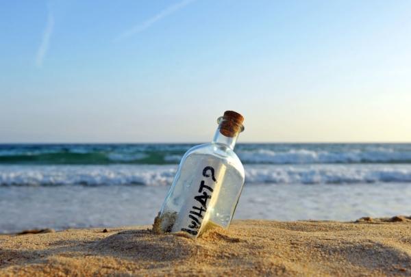 """Flaschenpost am Strand mit dem Wort """"WHAT?"""" auf der Schriftrolle."""