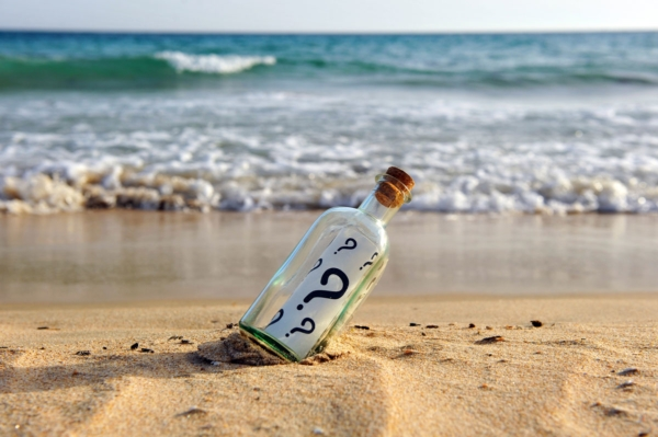 Flaschenpost am Strand mit dem mehreren Fragezeichen auf der Schriftrolle.