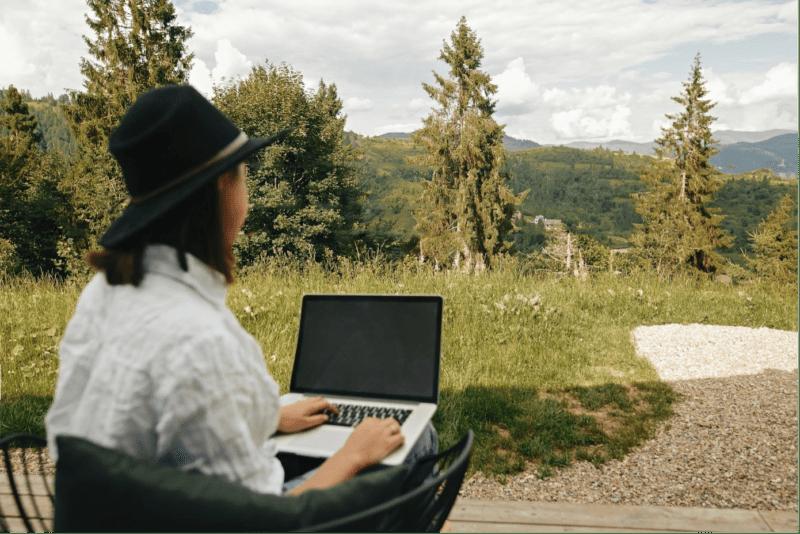 Frau im Grünen arbeitet am Laptop