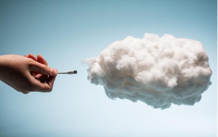 eine Hand steckt den Stecker in eine Wolke